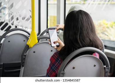 JAKARTA - Indonesia. March 20, 2019: Back view of young woman using a mobile phone while sitting inside the Transjakarta bus