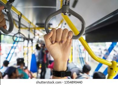 JAKARTA - Indonesia. March 20, 2019: Hands of female passengers holding handles on Transjakarta bus