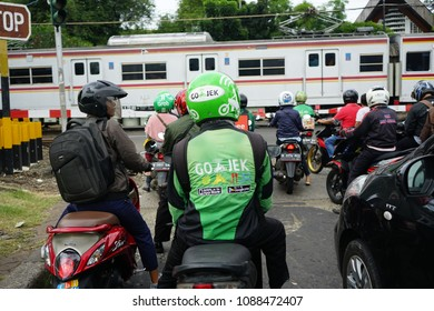Jakarta, Indonesia - March 27 2017: Driver wearing Helmet with Gojek Logo waiting for train passing. Gojek is Indonesian transportation startup