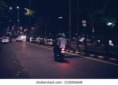 Jakarta, Indonesia - March 27 2017: Bike passengers wearing Helmet with Gojek Logo in the middle of night. Gojek is Indonesian transportation startup