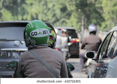 Jakarta, Indonesia - March 27 2017: Bike passengers wearing Helmet with Gojek Logo. Gojek is Indonesian transportation startup