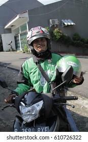 Jakarta, Indonesia - March 27 2017: Gojek Driver Holding Helmet. Gojek is Indonesian transportation startup