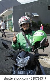 Jakarta, Indonesia - March 27 2017: Gojek Driver Holding Helmet and give thumbs up. Gojek is Indonesian transportation startup