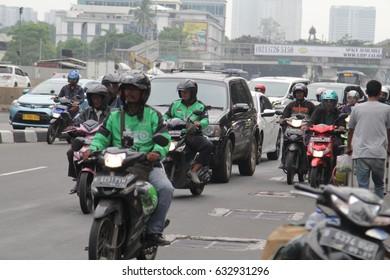 Jakarta, Indonesia - March 27 2017: Congested traffic, Gojek driving bike with passenger Gojek is Indonesian transportation startup.