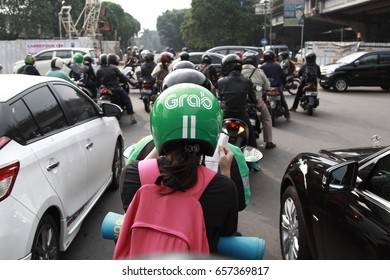 Jakarta, Indonesia - March 27 2017: Bike passengers wearing Helmet with Grab Logo. Gojek is Indonesian transportation startup