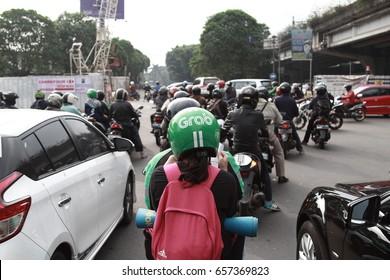 Jakarta, Indonesia - March 27 2017: Bike passengers wearing Helmet with Grab Logo. Gojek is Indonesian transportation startup