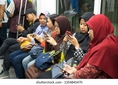 JAKARTA, Indonesia - March 27, 2019: Group of passengers using smartphone while sitting inside Jakarta MRT