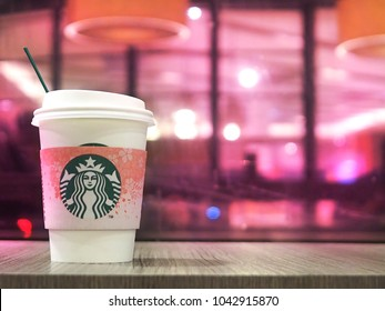 JAKARTA, INDONESIA: MARCH 8, 2018: A cup of Starbucks' hot coffee on a wooden table with blurry purple and pink cafe background