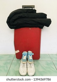 JAKARTA, INDONESIA. MAY 11, 2019. Mudik or  travel concept. Red Samsonite suitcase with black jacket and two pairs of child and adult shoes.