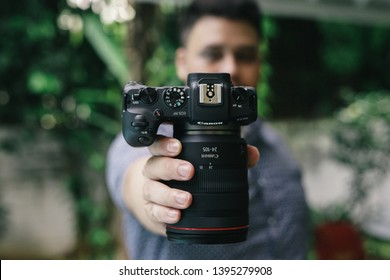 Jakarta, Indonesia - May 12, 2019: The young man holding a Canon EOS RP full frame mirrorless camera.