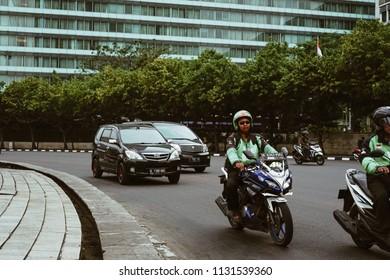 Jakarta, Indonesia - May 2 2018: Bike passengers wearing Helmet with Gojek Logo. Gojek is Indonesian transportation startup