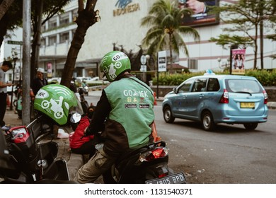 Jakarta, Indonesia - May 2 2018: Gojek driver waiting for passenger with helmet on the front. Gojek is Indonesian transportation startup
