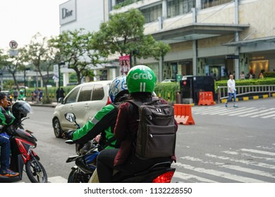 Jakarta, Indonesia - May 2 2018: Grab Bike Driver picking up passenger. Grab is a technology company that offers wide range of ride-hailing and logistics services through its app in Southeast A