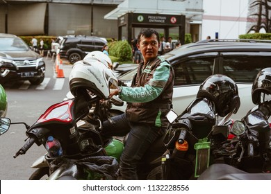Jakarta, Indonesia - May 2 2018: Grab Bike Driver waiting passenger. Grab is a technology company that offers wide range of ride-hailing and logistics services through its app in Southeast A