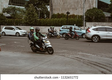 Jakarta, Indonesia - May 2 2018: View of a sudirman street with gojek a popular motorcycle taxi pass by. Gojek is Indonesian transportation startup
