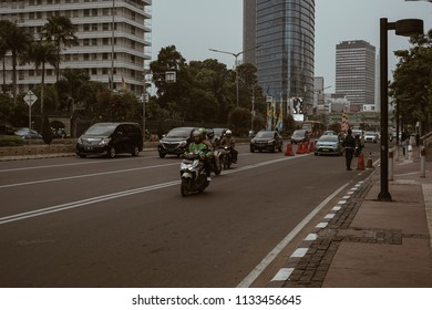 Jakarta, Indonesia - May 2 2018: Gojek driver and passenger in the middle of thamrin street. Gojek is Indonesian transportation startup