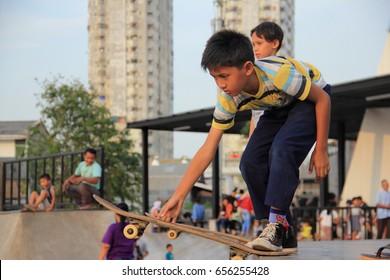 JAKARTA, INDONESIA - May 27th, 2017. Kids playing skateboard on Kalijodo, Jakarta, Indonesia