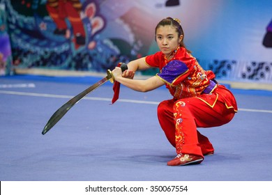 JAKARTA, INDONESIA - NOVEMBER 16, 2015: Fong Wei Chai of Malaysia performs the movements in the women's Daoshu event at the 13th World Wushu Championship 2015 at the Istora Senayan Stadium.