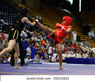 JAKARTA, INDONESIA - NOVEMBER 16, 2015: Puja Tomar of India (red) fights Luan Thi Hoang of Vietnam (black) in the men's 65kg Sanda event at the 13th World Wushu Championship 2015.
