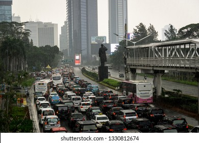 Jakarta, Indonesia - November 16 2018: Traffic jam along the Sudirman road in the heart of Jakarta business district on a rainy day with Transjakarta bus on their own busway.
