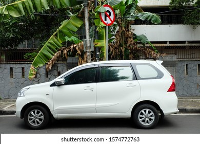 Jakarta, Indonesia - November 23 2019: A Single White SUV Car Breaks the Law by Parking on the No-Parking Area in Cikini, Jakarta, in the Afternoon