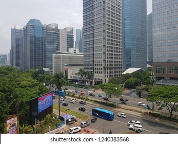Jakarta, Indonesia - November 25 2018: Traffic, including Transjakarta buses, drive along the modern Sudirman avenue in Jakarta business district