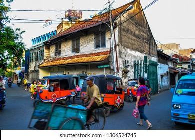 Jakarta, Indonesia - November 27, 2009: View of traffic near Jakarta China town or pecinan near petak Sembilan, with old building, Bajaj, mikrolet, becak and passerby