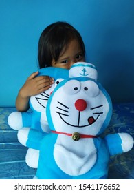 Jakarta, Indonesia - October 05 2019. Little girl hugging Doraemon doll with blue background the image is out of focus because it uses a smartphone camera