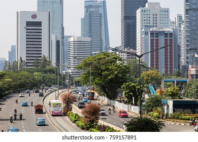JAKARTA, INDONESIA - OCTOBER 13, 2017: Traffic goes along Sudirman avenue, with a separte lane for the Transjakarta bus system, in Jakarta business district in Indonesia capital city.