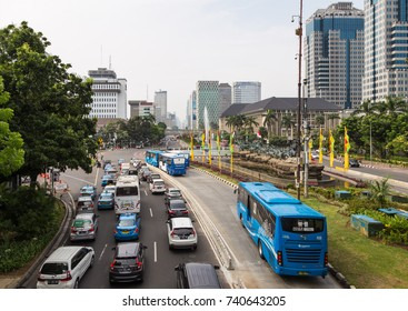 JAKARTA, INDONESIA - OCTOBER 16, 2017: A Transjakarta bus uses its dedicated traffic lane to avoid the heavy traffic on the Thamrin avenue in the business district of Jakarta, Indonesia capital city..