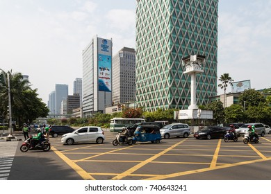 JAKARTA, INDONESIA - OCTOBER 16, 2017: Cars and motorcycles go through an intersection along the Thamrin avenue in the business district of Jakarta, Indonesia capital city.