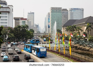 JAKARTA, INDONESIA - OCTOBER 16, 2017: A Transjakarta bus uses its dedicated traffic lane to avoid the heavy traffic on the Thamrin avenue in the business district of Jakarta, Indonesia capital city.