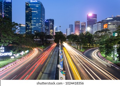 Jakarta, Indonesia - October 27 2017: Traffic, captured with blurred motion as light trails, rush along Sudirman street in Jakarta business district at night in Indonesia capital city.