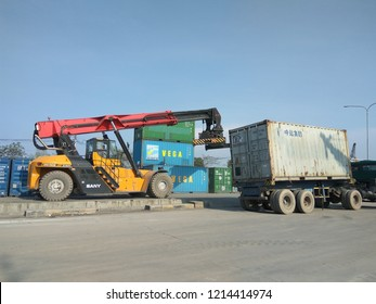 Jakarta, Indonesia - October 28, 2018: Crane vehicles are moving containers from trucks in the port of Sunda Kelapa, Jakarta - Indonesia