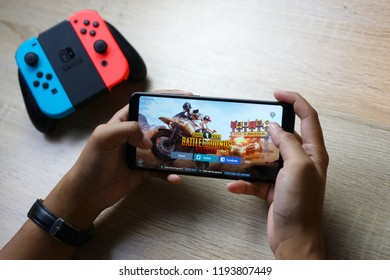 Jakarta, Indonesia - October 3, 2018: The Asus Zenfone Max Pro M1 with with Joy-Con controller Nintendo Switch in background playing PUBG Mobile battle royale mobile games.