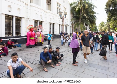 JAKARTA, INDONESIA - OCTOBER 9, 2016: People enjoy a walk on the pedestrian street of Jakarta old town. The large dolls are Ondel Ondel, a tradition of Jakarta.