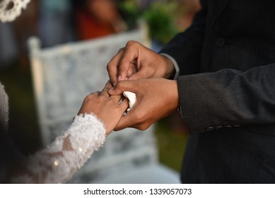 JAKARTA, INDONESIA - SEPTEMBER 03, 2017: The wedding of asian people, in a garden party concept, they as a christian. bride using beauty white dressand they give an marriage rings to each other.