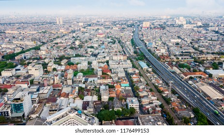 JAKARTA - Indonesia. September 04, 2018: Aerial view of crowded residential houses and highway with air pollution in Jakarta, Indonesia