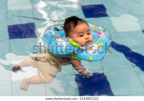 Jakarta, Indonesia - September 19, 2016: Cute Asian baby boy with baby floating neck ring learning to swim in the pool