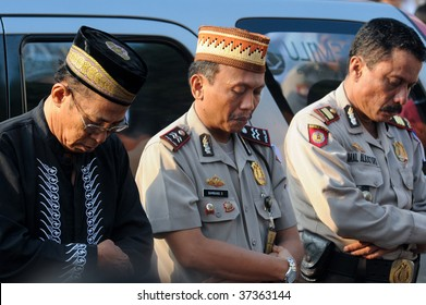 JAKARTA, INDONESIA - SEPTEMBER 20: Three Muslim men from the police force pray outside a mosque in Jakarta on Hari Raya, the end of a month of fasting called Ramadan September 20, 2009 in Jakarta.