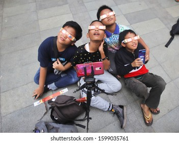 JAKARTA, INDONESIA-DECEMBER 2019-Visitors see a solar eclipse using special glasses at the Ismail Marzuki Park on December 26, 2019 in Jakarta.