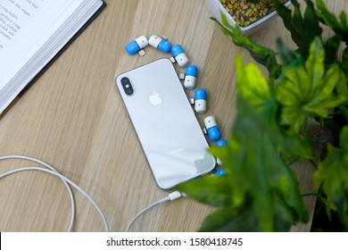 Jakarta- Indonesia,Wednesday 23 October 2019. iphone x is white on a wooden table with green plants and blue and yellow seeds