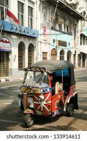 JAKARTA - SEPTEMBER 22: tuk tuk motorized rickshaw cheap form of public transport parked outside old colonial era buildings on September 22 2007 in Jakarta.
