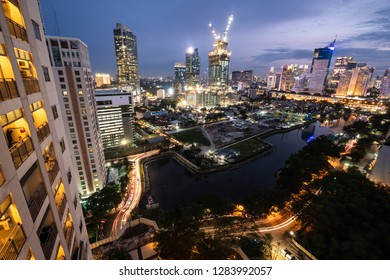 Jakarta skyline at night mixing modern skyscrapers, residential tower and traditional low rise residential in Indonesia capital city.