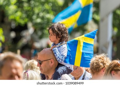 JAKOBSBERG, SWEDEN - JUNE 6, 2017:  Profile view of a little girl sitting on a mans shoulder holding a Swedish flag when celebrating the Swedish national day in Jakobsberg, Sweden June 6, 2017.