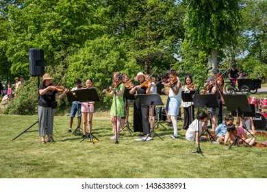 JAKOBSBERG, SWEDEN - JUNE 6, 2019: Garden view of adults and young people in an orchestra with instruments playing classical music together on the Swedish national day in Jakobsberg June 6, 2019.