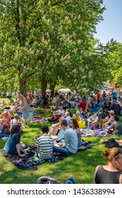 JAKOBSBERG, SWEDEN - JUNE 6, 2019: Summer garden view of people and families outdoors at a green field having picnic on Swedish national day. Diversity mixed ages in Jakobsberg Sweden June 6, 2019.