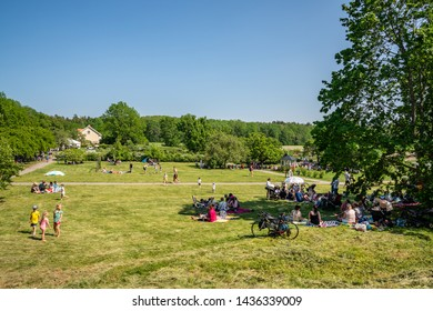 JAKOBSBERG, SWEDEN - JUNE 6, 2019: Rural landscape view of groups with many people outdoors at a green field having picnic in Jakobsberg Sweden June 6, 2019.