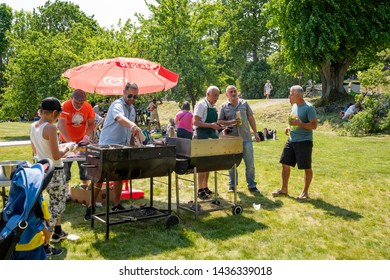 JAKOBSBERG, SWEDEN - JUNE 6, 2019: Close-up summer view of two males barbecue grilling outdoors on a green lawn in a park with people and parasols on Swedish national day in Jakobsberg June 6, 2019.