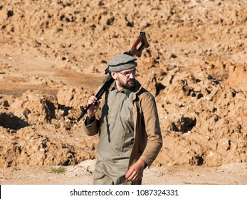 JALALABAD, AFGHANISTAN - OCTOBER 3, 2015: Afghan gunman put his rifle on his shoulder. ISIS militant near the city of Jalalabad on October 3, 2015